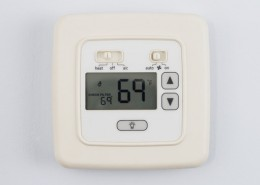 digital thermostat on light blue wall set to heating 69 degrees F