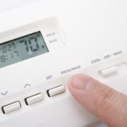Closeup shot of male hand adjusting thermostat to 70 degrees