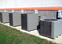 Row of commercial HVAC air conditioner outside compressor units outside a commercial building as part of a climate control cooling and refrigeration conditioning system